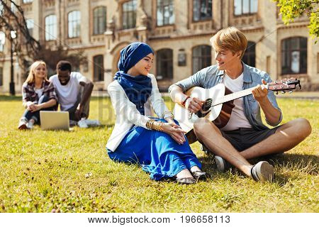 Lovely serenade. Lively charismatic imaginative guy meeting his friend after classes and resting on the grass while entertaining her with music