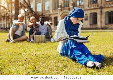 Cultural bullying. Intelligent strong progressive girl looking through the notes and getting ready for an exam while her fellow student making fun of her outfit