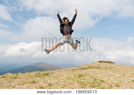 Handsome man hipster traveler with beard and moustache jumps on mountain top on blue cloudy sky bearded man