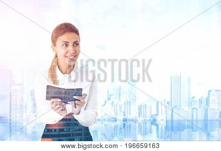 Portrait of an enthusiastic young woman holding a planner in both hands. She is smiling and standing against a blue cityscape. Toned image double exposure mock up