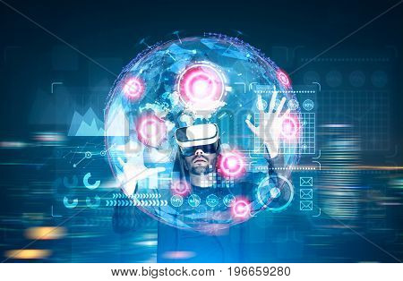 Glowing Earth hologram against a dark blue background with red placeholders and graphs. African American man in vr glasses toned image double exposure