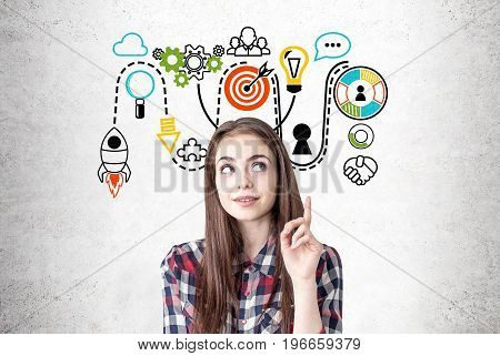 Portrait of a creative young woman wearing a checkered shirt and looking sideways while thinking and pointing upwards. Concrete wall background with a colorful start up sketch.