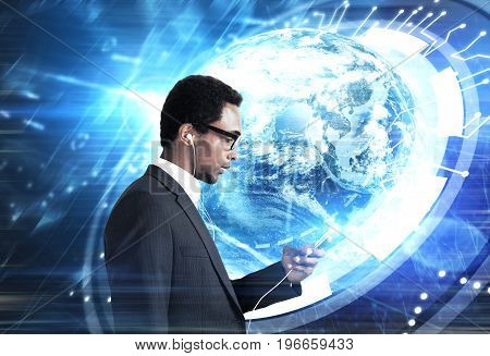 African American businessman holding a smartphone with headphones. Blurred blue background with a glowing HUD Earth. Toned image double exposure mock up.