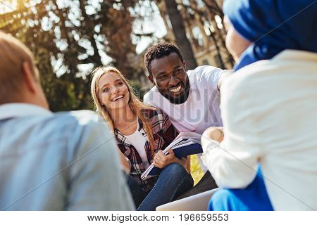 Different worldviews. Intelligent inspired humorous friends discussing something exciting while meeting up outdoors and sharing their stories