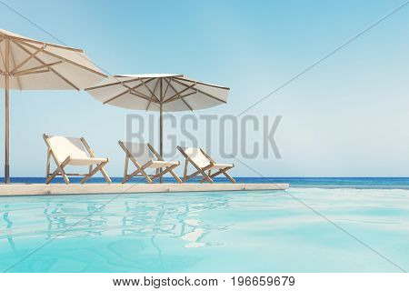 Three white deck chairs are standing under beach umbrellas near a swimming pool. A blue cloudless sky is above them. Side view. 3d rendering mock up