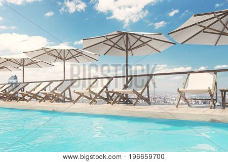 White deck chairs are standing under beach umbrellas near a swimming pool. A blue sky with clouds is above them. Side view. 3d rendering mock up