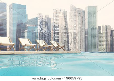 Row of white deck chairs near a swimming pool. Cloudless pale sky and a cityscape. 3d rendering mock up