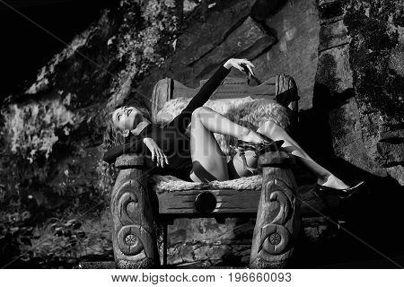 Woman In Big Wooden Arm Chair With Fur In Forest