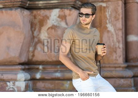 Pensive young bearded man in sunglasses is standing near old building and holding cup of coffee. He is leaning on handrail and looking aside. Copy space in left side