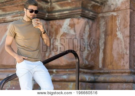Portrait of pensive young bearded guy in sunglasses leaning on metal handrail. He is looking down while drinking coffee. Old building on background. Copy space in right side