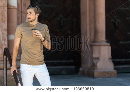 Portrait of pensive youthful guy with beard standing near huge metal gates of old building. He is holding by handrails and drinking coffee. Copy space in right side