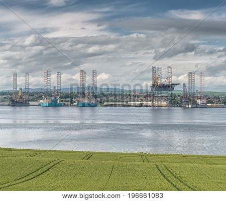 Offshore drilling platform in repair in shipyard in Dundee looking accross a green field and accross the River.