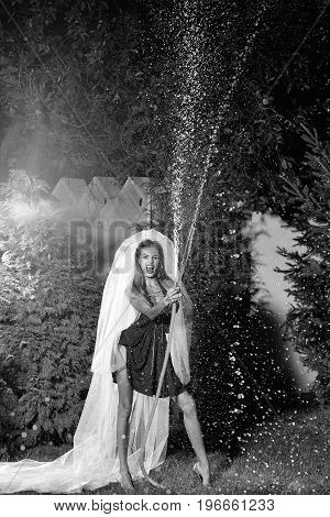 bride in dress and veil holding hose with water drops outdoor in evening black and white