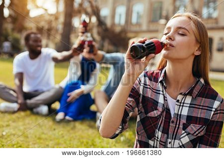 One more sip. Eager vibrant active woman spending the day outdoors with her friends and drinking refreshing drinks while enjoying it