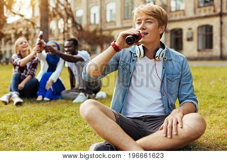 Quenching the thirst. Ambitious creative young guy trying new drink and enjoying it while spending the day outdoors with his friends