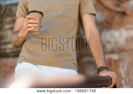 Close up of hands and body of young guy drinking coffee. He is standing beside building wall and holding by metal railing