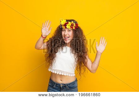 Brunette curly haired girl wearing chaplet white top jeans smiling holding hands up looking at camera.