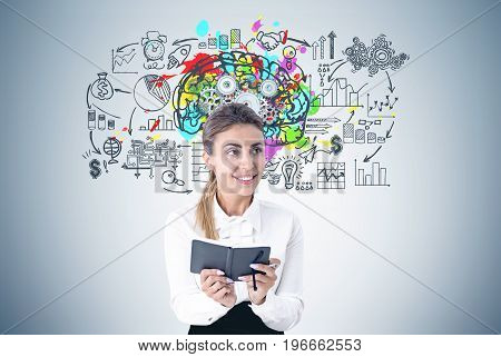 Portrait of an enthusiastic young woman holding a planner. She is smiling and standing near a gray wall with a business scheme and a colorful brain sketch with gears on it.