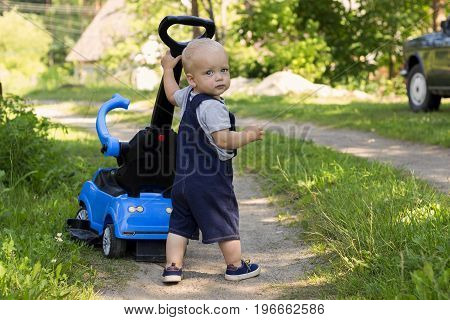 Funny one year kid with a car stroller walking in the garden.
