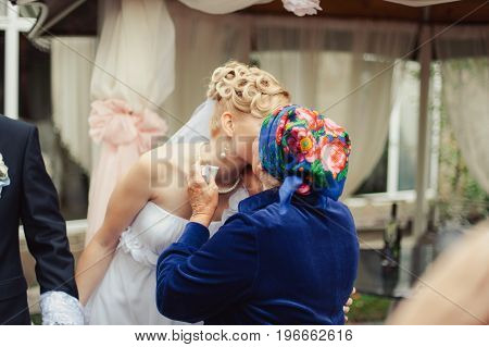 The Grandmother Kisses The Bride At Wedding