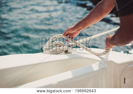 Man Tying Knot And Securing A Mooring For His Hobby Yacht Sail Boat