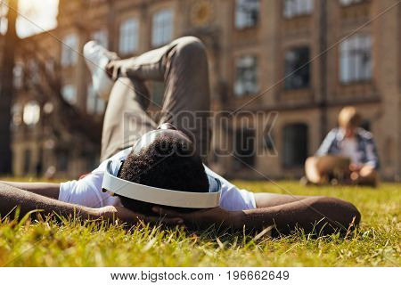 Perfect escape. Inventive awesome bright man lying on the grass and listening to the music while enjoying warm sunlight