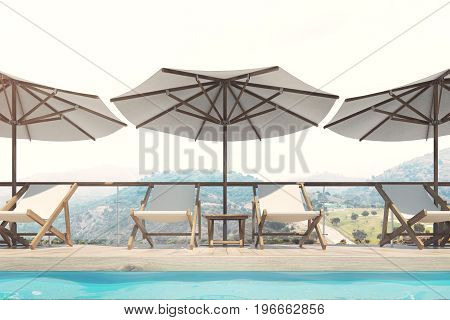 White deck chairs are standing under beach umbrellas near a swimming pool. A pale blue cloudless sky is above them. Close up. 3d rendering mock up