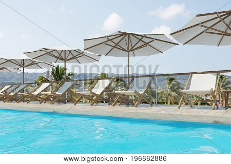 White deck chairs are standing under beach umbrellas near a swimming pool. A pale blue sky with clouds is above them. Side view. 3d rendering mock up