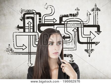Portrait of a thoughtful young woman holding a pen near her face and analyzing a challenging situation. Concrete wall with an arrow maze background.