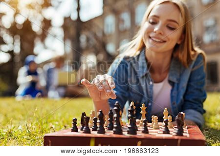 Careful tactics. Ambitious inventive brilliant lady developing a strategy while training her cognitive skills and playing chess with herself