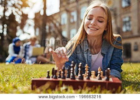 Training for the mind. Graceful diligent inspiring lady building up a strategy while playing chess and making the next move