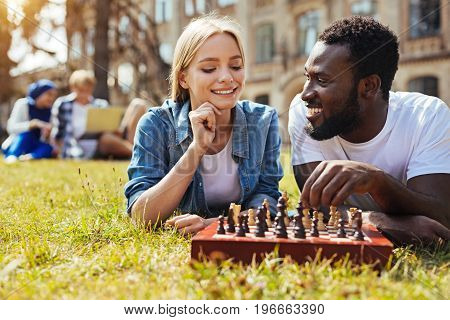 Brain games. Young capable productive lady explaining the rules of the game and trying making strategic moves while enjoying their free time together