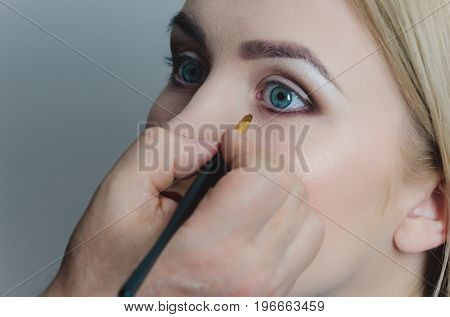 Woman With Blue Eyes Getting Makeup