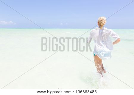 Young slim fit woman wearing white beach tunic running in sea water making water splashes with her legs. Vacation concept. Summer mood. Tropical beach setting. Paje, Zanzibar, Tanzania.