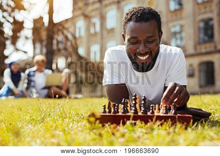 Brainy entertainment. Committed lively smart guy using chess for developing his thinking abilities and developing strategy