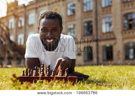 Join me. Handsome persistent joyful guy relaxing outdoors and playing chess while enjoying the process