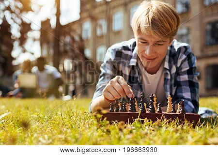 Strategic thinker. Handsome inspiring focused man using chess for keeping his mind in shape and developing his cognitive abilities