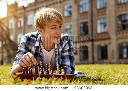 Fleshing up before study. Attractive brilliant talented man lying on the grass and playing chess while feeling happy and relaxed
