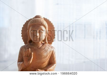 Wooden Buddha close eye with white background