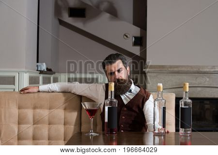 Man drinking red wine alone in restaurant. Bearded hipster with beard sitting at table with three bottles and glass. Alcohol abuse. Addictive and convive. Unhealthy lifestyle and bad habits