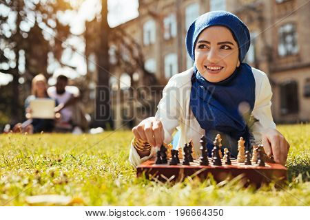 Intelligence and grace. Intelligent lively gorgeous lady lying on the grass and playing chess while relaxing after the day at the university