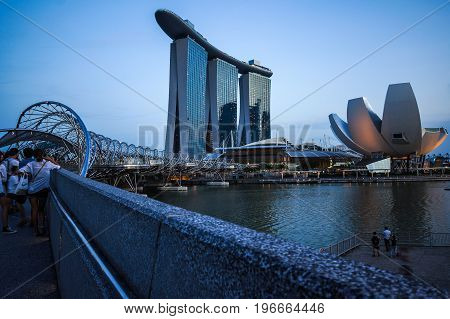 SINGAPORE - JUNE 17 2014 : Tourists on Bridge to Marina Bay Sands Hotel Singapore