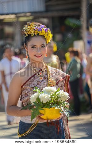 CHIANGMAI THAILAND - JANUARY 25 2015: Indigenous girl with local traditional costume with a bowl of white flowers in parade of 22nd Traditional Skirt Fabric and The Indigenous Product and Culture Festival in Mae Chaem Chiangmai Thailand