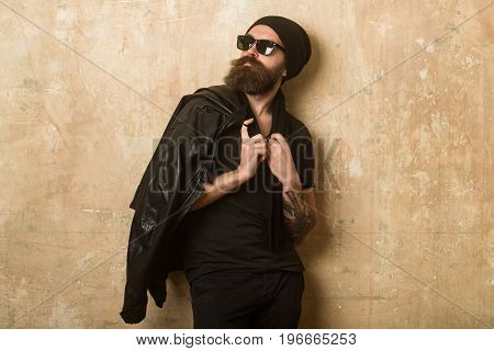 Biker fashion and beauty. Fashion model on textured wall background. Man with long beard and mustache. Hipster in leather jacket and hat with glasses. Guy with serious face.