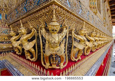 Along the inner walls of the Bangkok Palace complex Wat Phra Kaew temple a frieze of gilded Garudas hold the Naga snakes to protect the temple.