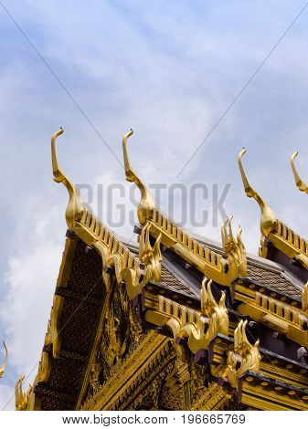 A row of Naga snake stylised scultpures ornates the pinnacles of this temple within the Royal Palace complex in Bangkok Thailand.