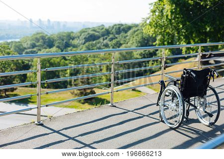Assistive device. Black shiny medical wheelchair left on a view point facing green park and a big city skyline