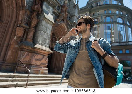 Jolly young bearded guy in sunglasses is walking along attractive medieval building. He is carrying backpack and talking via mobile phone with smile. Copy space in left side