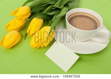 Bunch of yellow tulips with cup of coffee and gift card on green.
