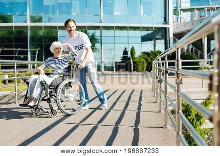 Sunlit path. Elderly disabled positive woman sitting in a wheelchair while the man taking her for a walk and managing the process